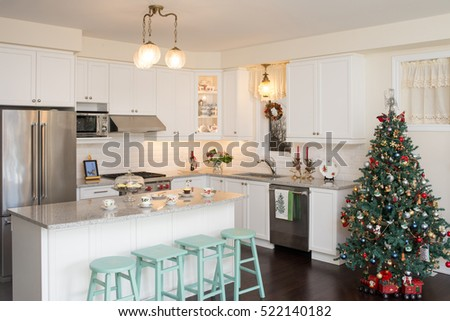 New white kitchen with Christmas decorations. Retro / antique style. Hand painted chairs with chalk paint, Christmas pattern English fine bone china teacups and plates. Decorated Christmas tree.