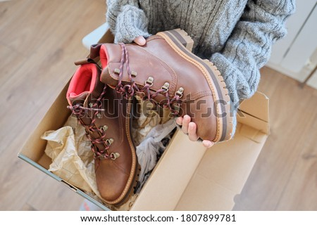 New womens leather brown waterproof hiking winter autumn boots in hands of female, trendy footwear for winter. Unpacking shoes, shopping online from home, shoe fashion store Foto stock ©