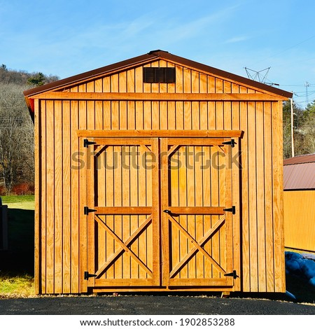 New wood shed on display. The shed is typically used as outdoor storage and commonly installed in home backyard Foto stock ©