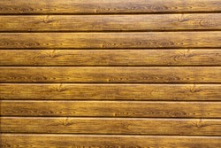 New wood surface with natural wood pattern. Wooden wall of the house, covered with varnish. Natural brown wood texture for background. Materials for wall cladding in construction and architecture.