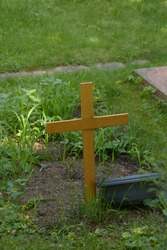 new wooden cross on an anonymous grave in a shady cemetery