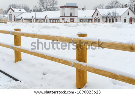 New wooden fence corral for outdoor horses. Fence of round wooden logs. Empty Horse paddock covered with snow. Farm equipment, carpentry Photo stock ©