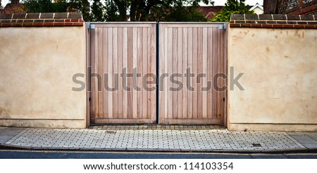 New wooden gate in a stone wall