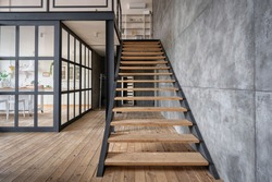 New wooden stairs in apartment house with modern interior design, near kitchen with glass wall