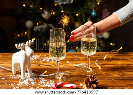 New year and Christmas decoration on the wood table .  Christmas deer on the wooden table with wineglasses and lights on the background, with bengal lights on the woman hand #776413597