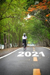 New year 2021 and sportswoman ride bike on road, Business challenge concept and keep going idea