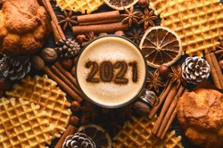 New year background. Number 2021 on frothy surface of cappuccino in coffee cup, cookies and spice. Food creative concept. Stylish cozy winter flat lay. Seasonal holidays concept. Top view