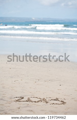 """New year background of beach with """"2013"""" drawn in the sand"""