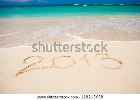 "New year background of beach with ""2013"" handwritten in the sand, holiday christmas concept"
