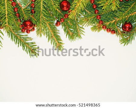 New Year background. Red balls toys and beads on a spruce. Decorated Green Christmas fir tree on white. #521498365