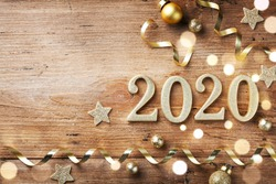 New Year celebration and festive background with golden numbers 2020, confetti stars and Christmas decorations top view.