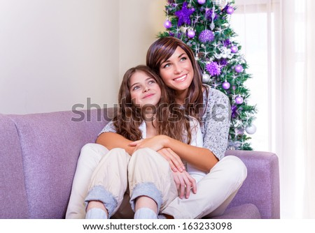 New Year celebration at home, mother sitting with daughter at home near Christmas tree and enjoying warm cozy Xmas evening