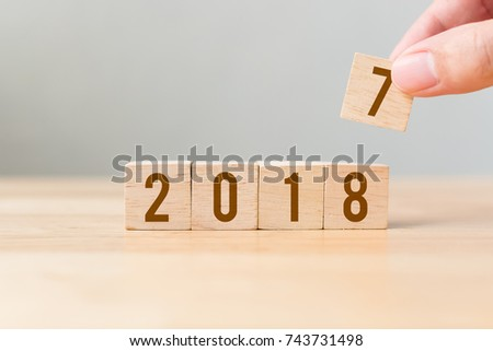 New year 2017 change to 2018 concept, Hand putting wood cube #743731498
