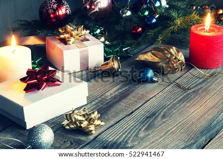 New Year, Christmas, gifts near a Christmas tree fluffy On a wooden table burning candles. Christmas decorations. Free space for text.