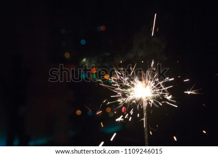 New Year Christmas sparkler on dark background with bokeh lights #1109246015