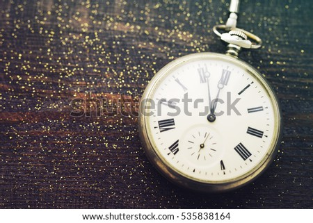 New year clock. Old pocket watch on a wooden background. New Year's background with hours over time 23:55. #535838164