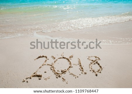 New Year 2018 coming concept - digits 2018 written on sand of beach and waves #1109768447