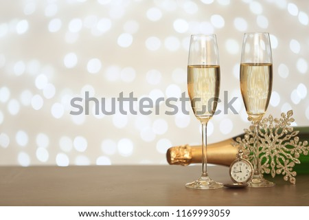 New year composition with champagne and space for text against blurred Christmas lights #1169993059