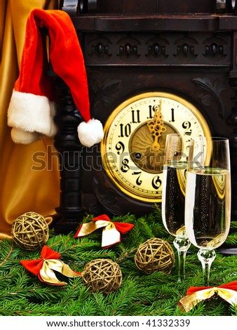 "New Year composition with old clock, champagne, ""Santa hat"", fir and decorations"
