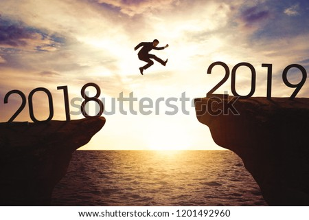 New year concept: Caucasian businessman jump through the gap between hill to the new year of 2019