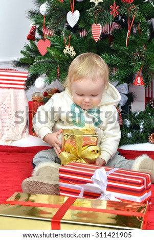 New year concept. Child baby toddler kid sitting under decorated christmas tree preparing presents gifts for celebration isolated on a white background