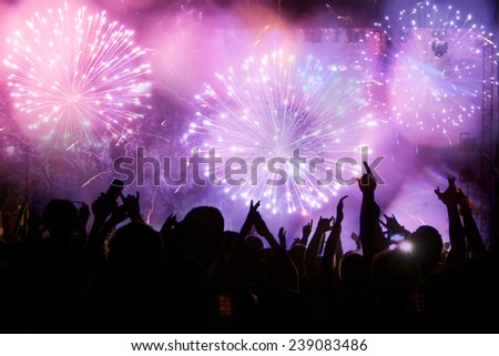 New Year concept - fireworks and cheering crowd celebrating the New year #239083486