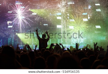 New Year concept - fireworks and cheering crowd celebrating the New year #516916135