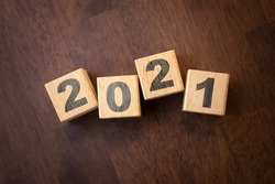 new year concept. font 2021 on wooden cubes on sunrise and bokeh green background for  banner with copy space for text. Leader or business manager trying for success idea.
