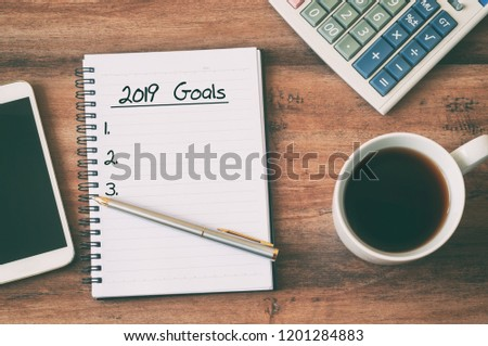 New year Concept - 2019 goals text on notepad. Smartphone, pen and cup of copy background.