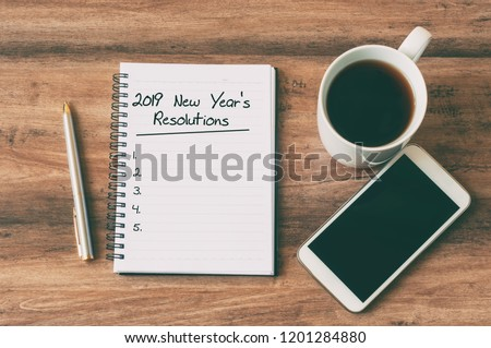 New year Concept - 2019 number and text on notepad. Smartphone, pen and cup of copy background.