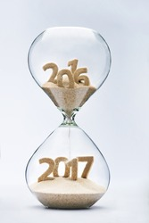 New Year 2016 concept with hourglass falling sand taking the shape of a 2017