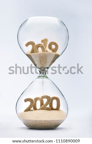 New Year 2020 concept with hourglass falling sand taking the shape of a 2020