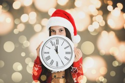New Year countdown. Cute little girl in Santa hat holding clock against blurred lights on background