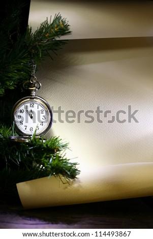 New Year decoration. Vintage pocket watch hanging near fir tree against blank scroll