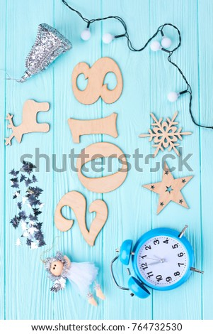 New Year 2018 decorations on wooden background. Cut out wooden digit 2018, Christmas lights, angel figurine, alarm clock, wooden silhouttes on blue wooden background, top view. #764732530