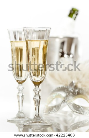 New Year fancy dress party with glasses of champagne and masquerade mask in high key