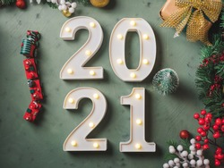 New year festive green background with 2021 illuminated numbers with ornament and toy train and tree decor on dark green.