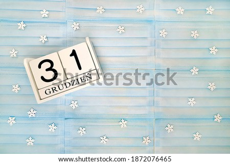 New year flat lay with blue medical mask and white wooden block calendar. Date 31 December in polish language (grudzień). Snowflakes on background. Zdjęcia stock ©