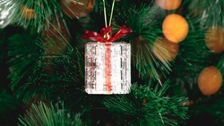 New Year gifts hanging on christmas tree, present boxes in Christmas celebrate winter season in holiday eve, Christmastime celebration, home decorated with festive shiny gift box.Donate, Ornaments.