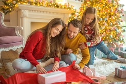 New year gifts. Young family sitting on the floor and packing new year gifts