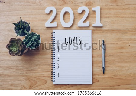 New year 2021 goals list. Office desk table with notebooks and pancil with pot plant.