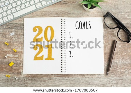 New Year goals List 2021 with notebook written in handwriting about plan listing of new year goals and resolutions setting. flat lay style. Christmas planning concept.