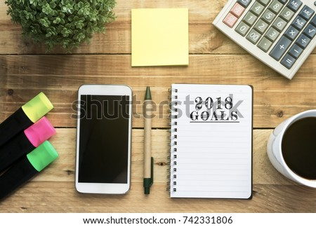 New Year 2018 Goals list written on a notepad with flat lay office desk and office supplies background.  #742331806