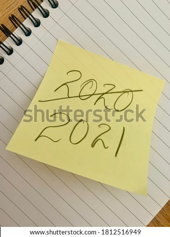 New year 2021 - goodbye 2020 message on a sticky note on a notepad.