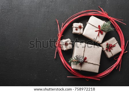 New Year greeting card and Christmas, space for a message of winter holidays with gifts for winter holidays in a red circle, you are ready for holidays, gifts on black background, made manually #758972218