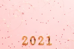 New Year 2021 greeting card. Flat lay of golden numbers and string lights on star pattern pink background. Copy space.