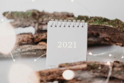 New Year 2021 grey calendar with lights in rustic natural style with tree bark