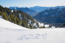 New year 2021, handwritten in snow, view to bavarian alps. Wallberg mountain.