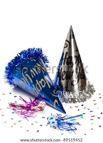 New year hats and party horn blowers with colorful confetti for holiday decoration.