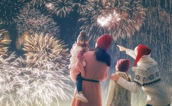 New Year holiday. Parents and daughters children girls are watching fireworks. Happy family on snowy winter walk in nature. Holidays winter season.